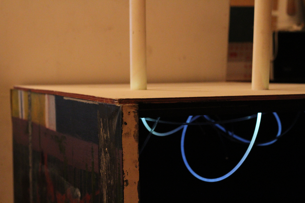 a photograph of an interactive artwork. The artwork is in the form of a large box, like a table. This close-up shot only shows some of the left side and the top of the box, and also an opening into the underneath/inside where the side facing us should be. The left side is an abstract painting with mostly dark colours. The top has two tubes placed in it. The underneath shows a series of bluish pipes of light that seem to emanate from the tubes above.