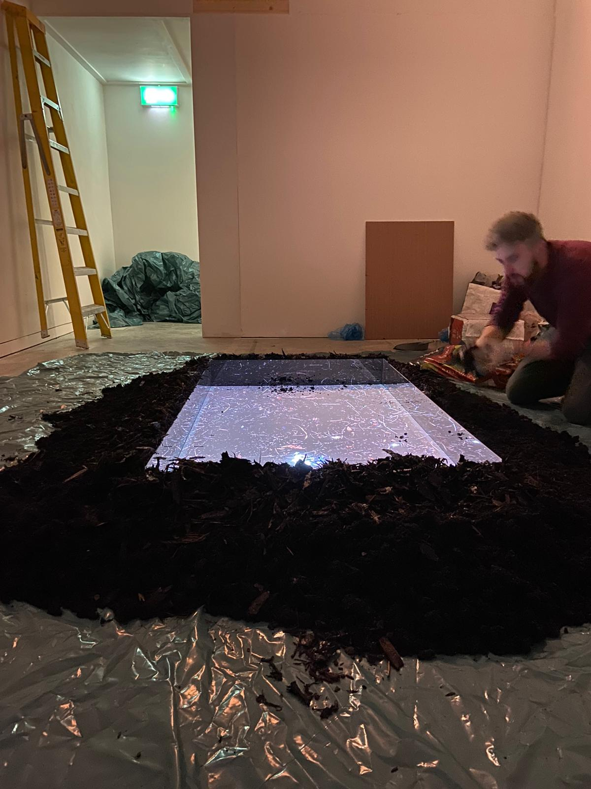 Photograph of the artist installting new artwork Reappropriation at the Regional Cultural Centre, Letterkenny