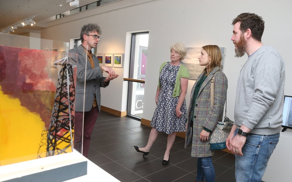 shane finan at the opening for over nature in cork, standing with one of his paintings