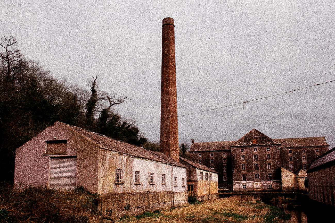 An edited image of a defunct factory with a grainy and intentionally postapocalyptic style